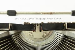 Typewriter and they lived happily. The text And they lived happily ever after, on a white paper page in an old vintage typewriter. Macro detail shot royalty free stock photos