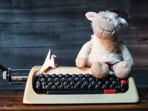 Typewriter with paper bird and Dolly the sheep. On wood and wood background stock image