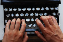 Typewriter. Photo of hand on the antique typewriter keys Royalty Free Stock Image