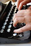 Typewriter. Photo of hand on the antique typewriter keys Stock Photo