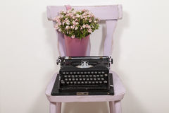 Typewriter. On a pink chair with flowers royalty free stock image