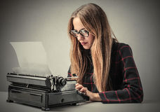 Typewriter. Portrait of woman writing with a typewriter royalty free stock photography