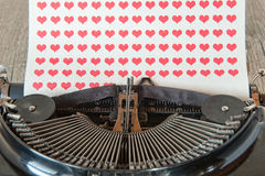 Typewriter with red hearts on paper Stock Image