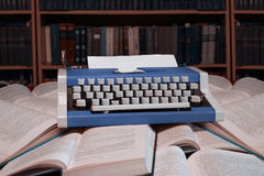 Typewriter standing in open books  with blank sheet of paper wit Stock Photo