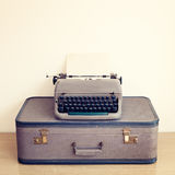 Typewriter and vintage suitcase stock photo
