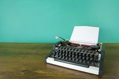 Typewriter. Vintage typewriter on wooden desk. Mint green background royalty free stock image