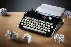 Typewriter and writers block. Frustration stress and writers block with old typewriter on desk and crumpled paper ball Stock Photo