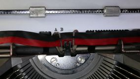 TYPEWRITER with written ABCDEFG in the paper. Old typewriter with written ABCDEFG with black ink in paper stock footage