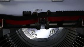 TYPEWRITER with written Success in the paper. Old typewriter with written Success with black ink in paper stock footage