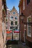 Typical alley in Alkmaar Netherlands with view at Canal and Canal House. Typical alley and historical Dutch houses in Alkmaar Netherlands with view at Canal and royalty free stock images