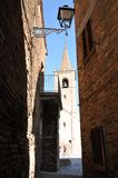 Medieval village of Castignano in central Italy. Typical alley and bell tower of the church of San Pietro Apostolo in the medieval village of Castignano in the royalty free stock photo
