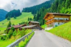 Typical alpine building oon green meadow, Austria stock photos