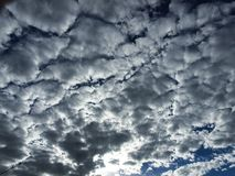 Typical Altocumulus cloud formationin blue sky. A delightful brightly coloured cloudy sky cloudscape featuring a typical Altocumulus cloud formation in a mid stock image
