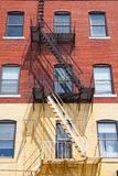 The typical american fire escape ladder zigzagging across the fa. Ce and windows.Portland, USA Stock Photography