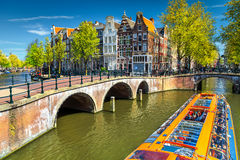 Typical Amsterdam canals with bridges and colorful boat, Netherlands, Europe. Stunning Amsterdam canals and typical dutch houses in capital of Netherlands Stock Images