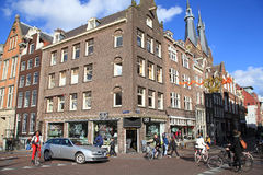 Typical Amsterdam street with old dutch buildings and cyclists Stock Images