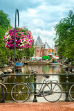 Typical Amsterdam view. With bikes, canals and historical buildings. In the back, Nieuwmarkt square is dominated by the gate of the medieval city royalty free stock photography
