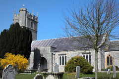 Typical, ancient church in Dorset England. Traditional English church with graveyard, headstones and trees on a bright sunny day Royalty Free Stock Images