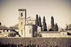 Typical ancient italian Romanesque church immersed in the Tuscany countryside near a Cemetery - Italy - Toned Image.  stock photos