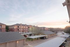 Typical apartment complex with detached garage and covered parking lots at sunrise. Aerial view of apartment complex with detached garage and covered parking stock photo