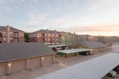Typical apartment complex with detached garage and covered parking lots at sunrise. Aerial view of apartment complex with detached garage and covered parking stock images
