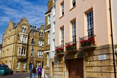 Typical architecture of england in oxford. Honey colored buildings with beautiful red flowers in balcony Stock Photography