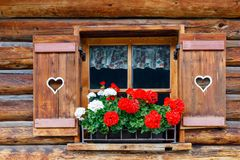 Typical bavarian or austrian wooden window with red geranium flowers on house in Austria or Germany.  Stock Photos
