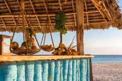 Typical beach bar at Zanzibar. In the picture beach bar in Nungwi ( Zanzibar ) at sunset , with exposed coconut , banana and tropical fruit .This bar is made Royalty Free Stock Image