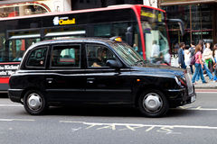 A typical black cab in Regent Street. In London. The London's iconic black cabs are a symbol of the city and a major attraction in themselves royalty free stock images