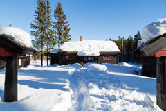 Typical black Norwegian cabin with path made in deep snow Royalty Free Stock Image