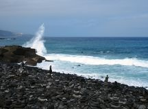 Typical black volcanic beach in the tenerife with deep blue sea and a wave breaking over rocks with stacked stones Royalty Free Stock Photo