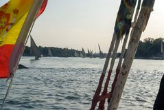 Typical boats of the Nile river called felucca seen from one of them with the Spanish flag. In sunset Stock Image