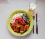 Typical Bolivian food. stewed chicken stuffed with spicy sauce served with steam rice, dried potatoes and salad with tomatoes and Stock Image