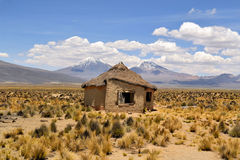 Typical Bolivian house with volcanoes Royalty Free Stock Photography