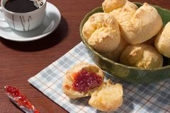 A brazilian cheese bread in a green bowl with a white cup of black coffee and a rasbarry jam in a knife pao de queijo. Typical brazilian cheese bread, called pao Royalty Free Stock Photo