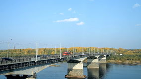 A typical bridge in Russia over the river. Across the river a bridge is thrown, cars are moving on it stock video footage