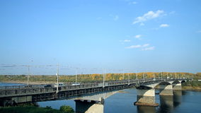 A typical bridge in Russia over the river. Across the river a bridge is thrown, cars are moving on it stock footage