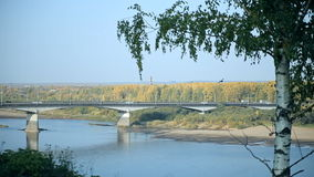 A typical bridge in Russia over the river. There is a birch in the foreground, a river is behind it. Across the river a bridge is thrown, cars are moving on it stock video footage