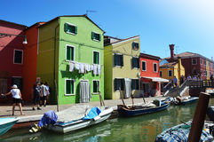 Typical brightly colored houses and narrow channels with tourists in Burano, Venice, Italy. BURANO, ITALY - AUGUST 9, 2016: Typical brightly colored houses and Royalty Free Stock Images
