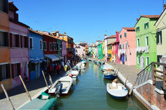 Typical brightly colored houses and narrow channels with tourists in Burano, Venice, Italy. BURANO, ITALY - AUGUST 9, 2016: Typical brightly colored houses and Stock Image