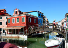 Typical brightly colorful houses and narrow channels with tourists in Burano, Venice, Italy. BURANO, ITALY - AUGUST 9, 2016: Typical brightly colorful houses and Stock Photography