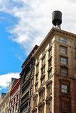 Typical Brooklyn neighborhood building with a wooden water tank on its roof, New York city Royalty Free Stock Photos