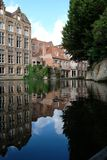 Typical canal scene in Bruges / Brugge, Belgium showing medieval buildings overlooking the water. Photographed on a sunny day in portrait royalty free stock images