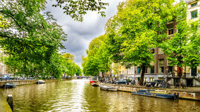 Typical Canal Scene in the old city of Amsterdam. Typical Canal Scene with Historic Houses dating back to the Middle Ages along the canals in the old city of royalty free stock image