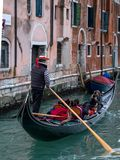 Typical canal scene in Venice Italy with gondola, gondolier and tourists. royalty free stock photography