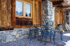 Typical chalet in the alps. Old window, chairs and table in front of a traditional cottage in the french alps Royalty Free Stock Photos