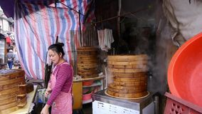 Typical chinese bun stand,a woman count the money,fresh buns with steam. stock video