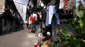 Typical Chinese old town street,china old woman leisurely sitting in a chair. Typical Chinese old town street,china elderly leisurely sitting on a chair in the stock video footage