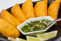 Typical Colombian empanadas served with spicy sauce. On traditional black ceramic dish Royalty Free Stock Photo