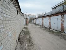 Typical complex of old concrete garages with closed metallic doors in Russia. driveway road through garages with. Perspective royalty free stock images